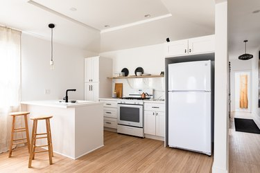 Minimalist kitchen with white walls and cabinets, wood floors and black accents