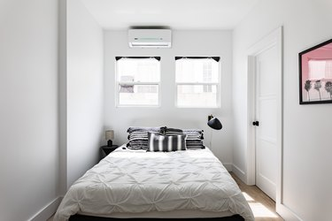 Ductless minisplit air conditioner in a minimalist white walled bedroom with white bedding and black accents