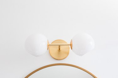 Gold wall sconce with globes over a mirror