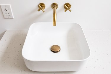 A white sink basin with a gold faucet and handles