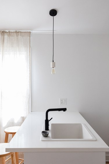 Minimalist white kitchen island with a black faucet and a lightbulb pendant light