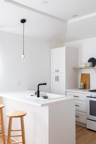 A white walled kitchen with white cabinets and counters and black accents