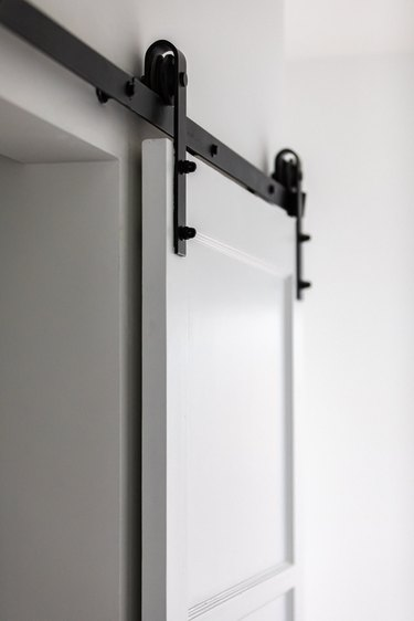 A white sliding door with black hardware hinges