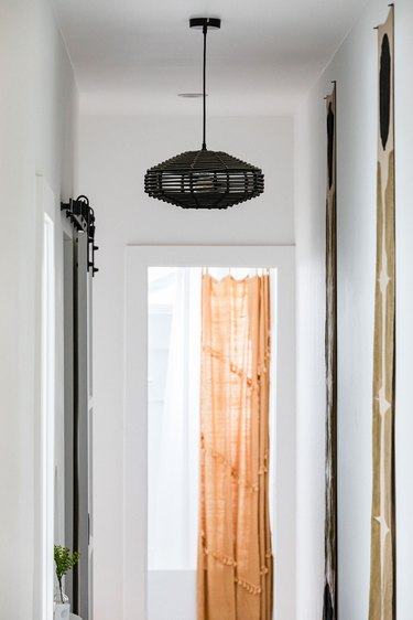 Hallway Lighting Ideas with A black abstract pendant light in a white-walled hallway and an orange curtain
