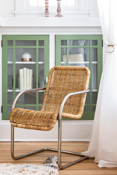 Corner of a living room with a wicker armchair on a wood floor with green cabinets