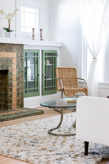 Contemporary living room with a tiled fireplace, wood floors and green cabinets