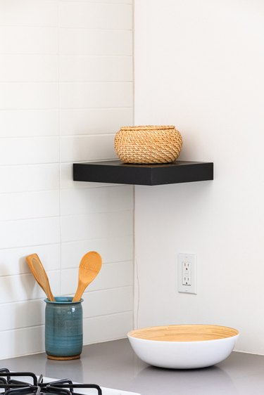 Black shelf with a wicker bowl and a gray kitchen countertop with dishware