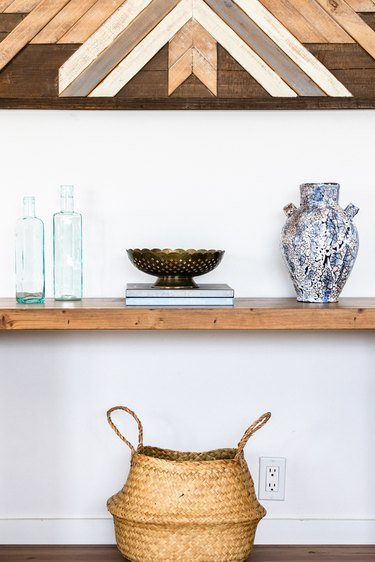 Hallway Wall Decor Ideas in hall with A wood wall hanging over a wood shelf with vases and a fiber basket