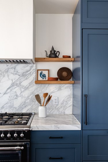 Dark blue kitchen cabinets, marble counter and backsplash, gas range, open shelves.