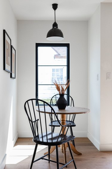 A window with black trim in front of a kitchen table and chairs