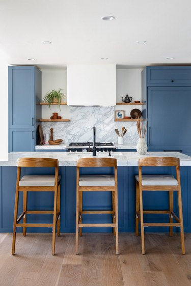 A kitchen with blue cabinets and wood bar stools at a kitchen island
