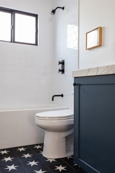 white toilet, blue vanity with marble countertop, blue tile floor with white star pattern, white bathtub, white subway tile, black faucet and showerhead, small window