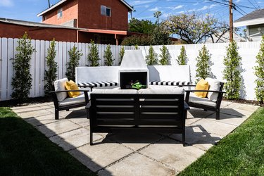 a paver patio with black and white outdoor patio chairs, a white privacy fence with evenly spaced small green trees