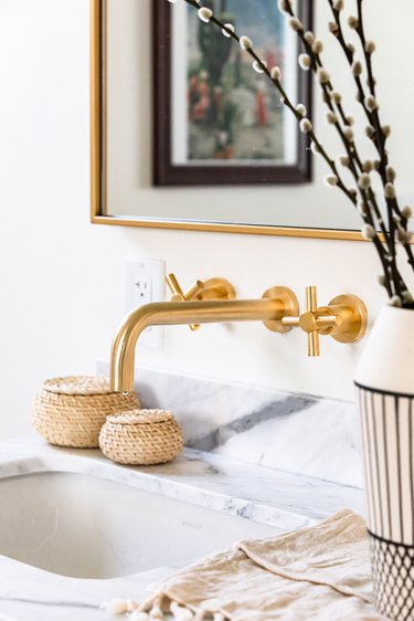 Gold sink faucets over a white countertop and a black and white vase with willow cuttings