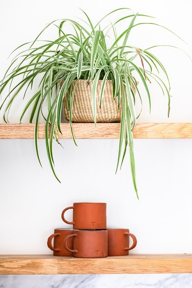 Terra-cotta mugs on a wood shelf and a plant in a wicker basket