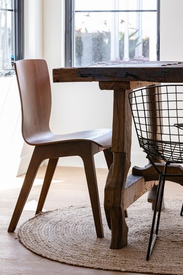 A wood chair and black wire chair at a wood dining table and a round jute rug
