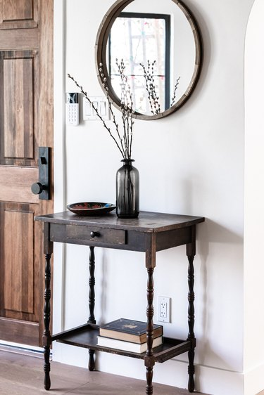 A side table with a black vase of willow cuttings and a round mirror and wood door
