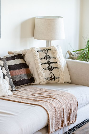 A white living room sofa with beige-black pillows and a beige blanket