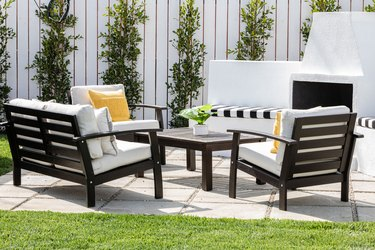 Brown frame patio furniture with white cushions and yellow pillows with a fireplace