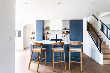kitchen with blue cabinets and marble backsplash