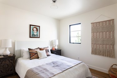 Small bedroom with lamps, nightstands, wall hanging, art
