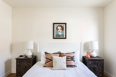 white bedroom white white bed, painting of red-haired woman, and dark wood nightstands
