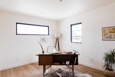 home office with midcentury wood desk and floor lamp with swivel chair
