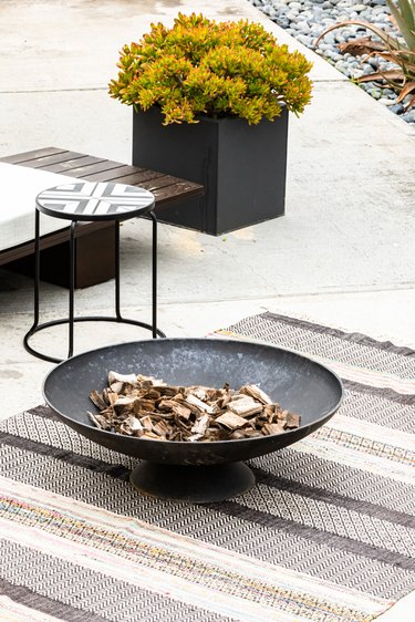 A patio fire pit on a gray-neutral striped rug with a plant and stool