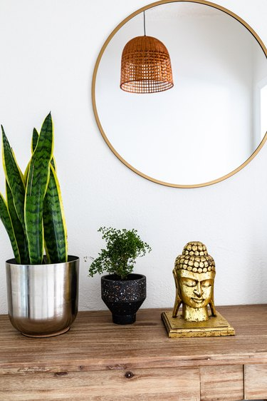 A large round mirror over a wood dresser with a gold buddha and plants
