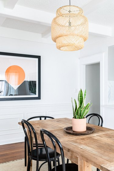 Dining room with a wood dining table, snake plant, wicker pendant light and art