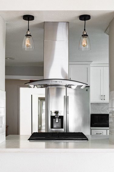 Minimalist kitchen with white cabinets and black pendant lightbulb lights