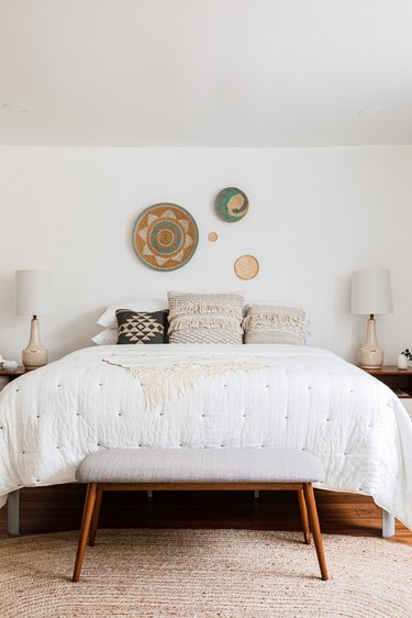 A boho, minimalist bedroom with knitted bedding and woven wall decor