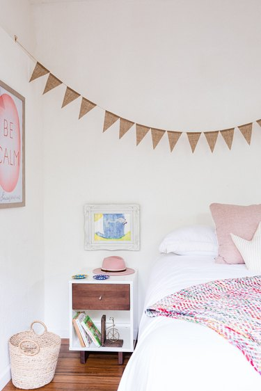 A white-walled bedroom with pink accents and wood floors