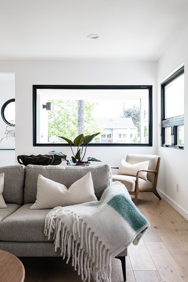Grey couch with white fringed blanket in modern living room with large black-framed windows and hardwood floor
