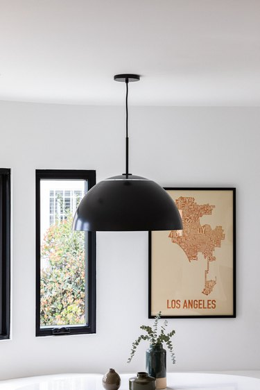 Black contemporary dining room lighting against curved white wall with framed print and window above round white table with plants