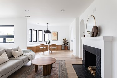 Modern living room with couch, rug, fireplace, and coffee table leading to dining room with pendant lamp, curved bench, and table set