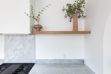 Shelving unit with two small plants over marble backsplash above black stovetop and marble countertop against white wall