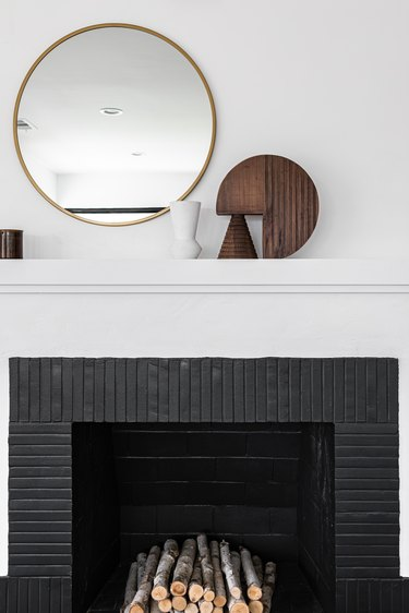 White mantle above black fireplace with wood sculptures next to round mirror against white wall