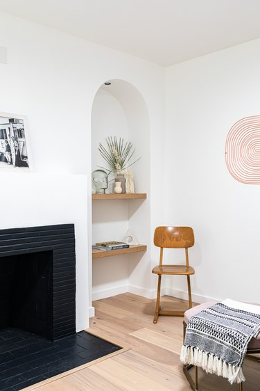 Corner of contemporary living room with black fireplace, alcove with wood shelves and plants, wood desk chair, and hung art