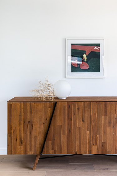 hallway lamp idea with Wood paneled cabinet with globe light against white wall with small hung painting on hardwood floor