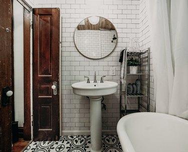 Pedestal Sink Storage Ideas in Bathroom with white pedestal sink, white subway tile, clawfoot tub, round mirror, metal shelves.