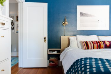 Bedroom with bright blue walls, gold sconce and a white door.