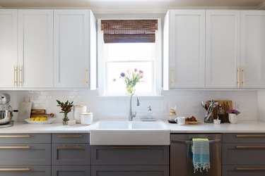 Gray and white cabinets, in a kitchen with a farmhouse sink, vases of flowers.