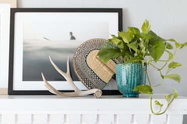 plant in green planter on white mantel