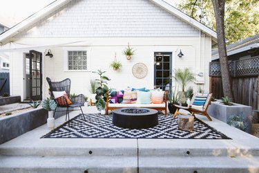 Patio with a black and white zig-zag rug, eclectic Modernist chairs, plants, and a fire pit.