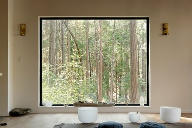 A large picture window with a forrest view, and crystals. A neutral rug with blue cushions, and white meditation singing bowls.