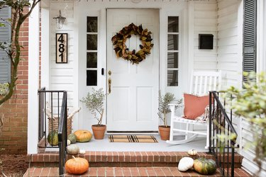 Porch with an autumnal door wreath, tree plants, basket of birch logs, and pumpkins