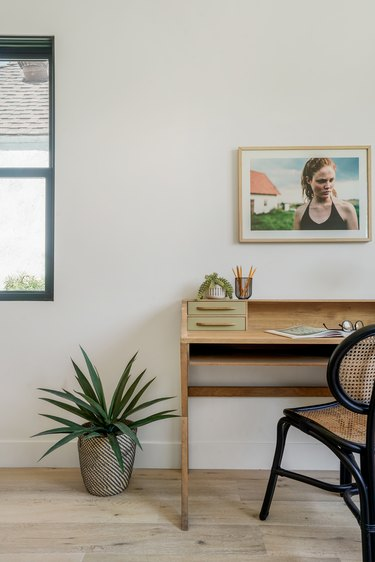 Wood desk with a black frame and cane chair. Framed photo art above. A plant in a gray vase on light wood floor and black frame window