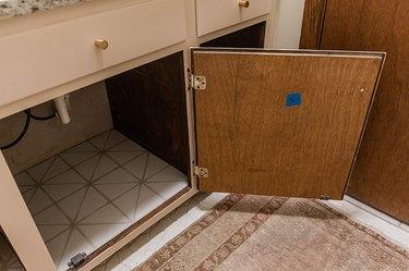 Open wood door of a bathroom vanity cabinet