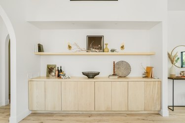 Large wall niche with a light wood sideboard and shelf with art and accent pottery